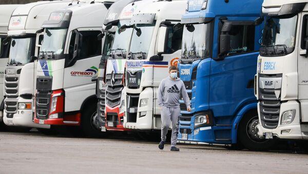 A driver wearing a face mask walks past lorries at Ashford International Truck Stop, as EU countries impose a travel ban from the UK following the coronavirus disease (COVID-19) outbreak, in Ashford, Britain 22 December 2020. - Sputnik International