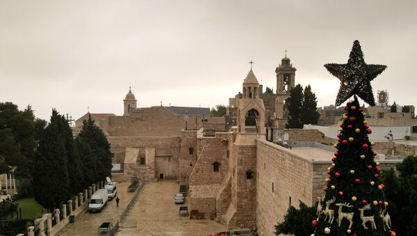 A picture taken with a drone shows the Church of the Nativity and a Christmas tree at Manger Square on Christmas Eve, in Bethlehem in the Israeli-occupied West Bank 24 December, 2020. - Sputnik International