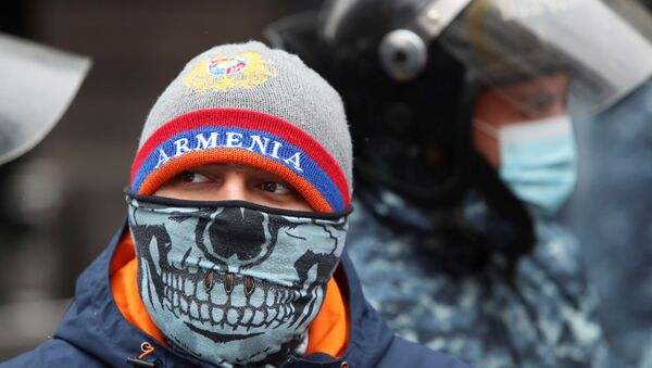 A participant wearing a face mask stands next to Armenian law enforcement officers outside the government office during an opposition rally to demand the resignation of Prime Minister Nikol Pashinyan following the signing of a deal to end a military conflict over Nagorno-Karabakh in Yerevan, Armenia December 24, 2020.  - Sputnik International