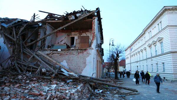 People walk past a collapsed building after an earthquake, in Petrinja, Croatia December 29, 2020.  - Sputnik International