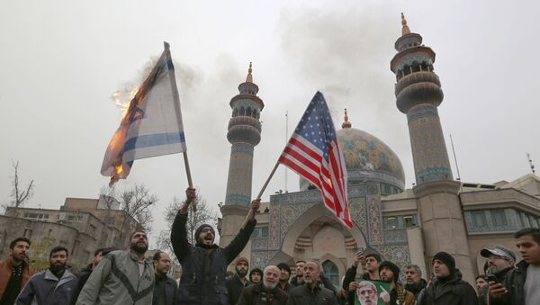 Iranians burn an Israeli and a US flag during an anti-US protest over the killings during a US air stike of Iranian military commander Qasem Soleimani and Iraqi paramilitary chief Abu Mahdi al-Muhandis, in the capital Tehran on January 4, 2020. - Sputnik International
