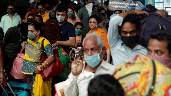 FILE PHOTO: People wearing protective masks leave a railway station amid the spread of the coronavirus disease (COVID-19) in Mumbai, India, 11 December 2020. REUTERS/Francis Mascarenhas/File Photo - Sputnik International