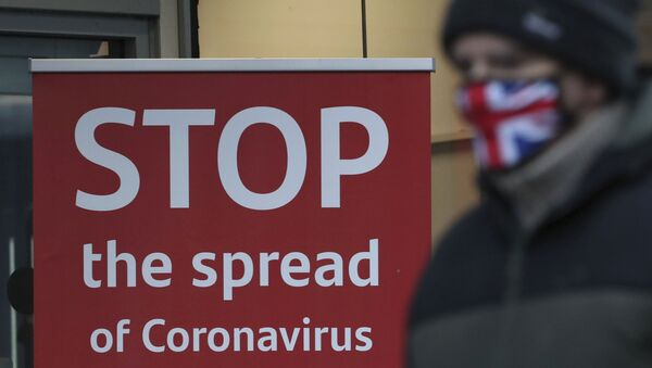 A man wearing a British union flag face mask walks past a coronavirus advice sign outside a bank in Glasgow the morning after stricter lockdown measures came into force for Scotland, Tuesday Jan. 5, 2021.  Further measures were put in place Tuesday as part of lockdown restrictions in a bid to halt the spread of the coronavirus. - Sputnik International
