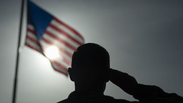 In this photo taken Aug. 26, 2019 and released by the U.S. Air Force, U.S. Air Force Staff Sgt. Devin Boyer, 435th Air Expeditionary Wing photojournalist, salutes the flag during a ceremony signifying the change from tactical to enduring operations at Camp Simba, Manda Bay, Kenya - Sputnik International