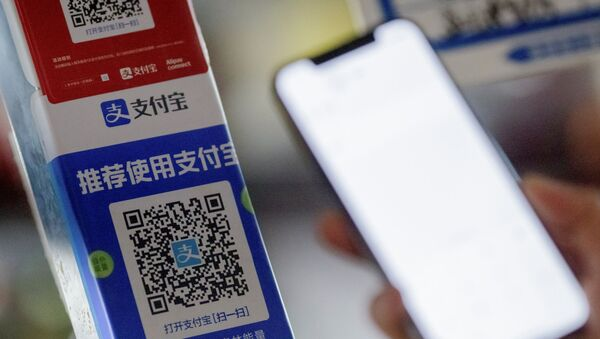 Customer uses a phone to scan the QR code of the electronic payment service Alipay that belongs to Ant Group Co Ltd at a market stall in Beijing, China, December 31, 2020 - Sputnik International