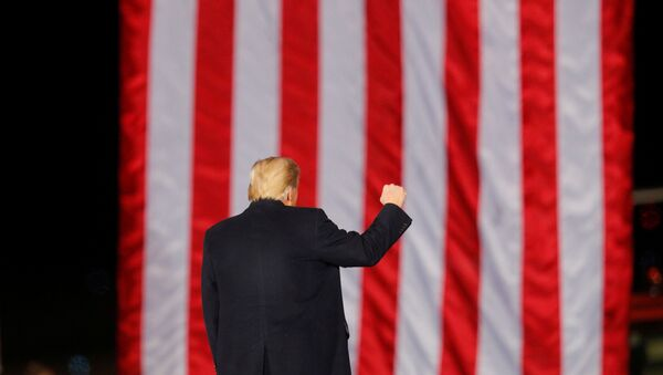 U.S. President Donald Trump gestures in front of a U.S. flag while campaigning for Republican Senator Kelly Loeffler on the eve of the run-off election to decide both of Georgia's Senate seats, in Dalton, Georgia, U.S., January 4, 2021. - Sputnik International