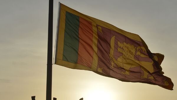 Sri Lankan soldiers stand at attention as their national flag is lowered as part of a daily ceremony at the Galle Face Green promenade in Colombo on July 20, 2018.  - Sputnik International