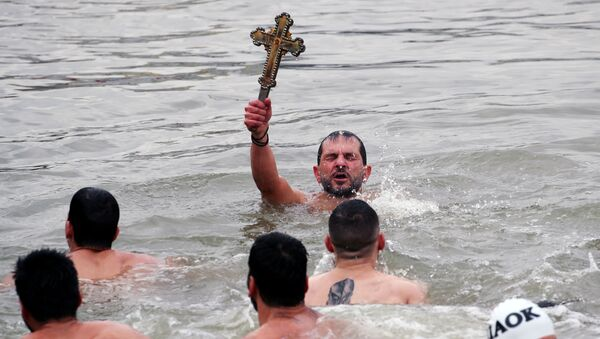 Greek Orthodox faithful Michalis Vosnauidis, a pilgrim from Thessaloniki, Greece, retrieves a wooden crucifix as he swims in the Golden Horn during the Epiphany ceremony in Istanbul, Turkey, January 6, 2019.  - Sputnik International