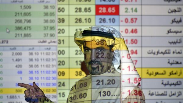 In this Thursday, Dec. 12, 2019, file photo, a trader talks to others in front of a screen displaying Saudi stock market values at the Arab National Bank in Riyadh, Saudi Arabia.  - Sputnik International