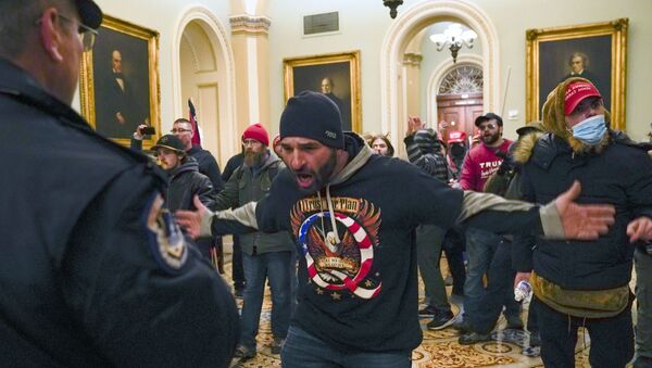Trump supporters gesture to US Capitol Police in the hallway outside of the Senate chamber at the Capitol in Washington, Wednesday, Jan. 6, 2021 - Sputnik International