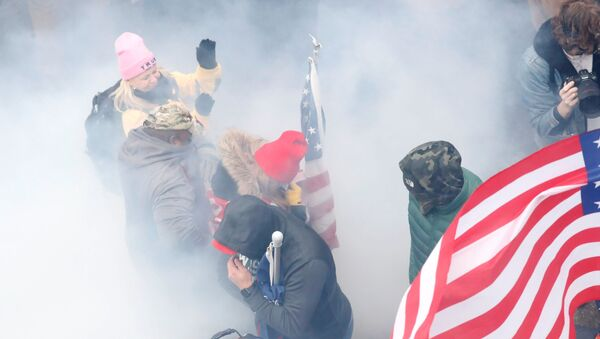 Pro-Trump protesters react amidst a cloud of tear gas during clashes with Capitol police at a rally to contest the certification of the 2020 US presidential election results by the US Congress, at the US Capitol Building in Washington, US, January 6, 2021. REUTERS/Shannon Stapleton - Sputnik International