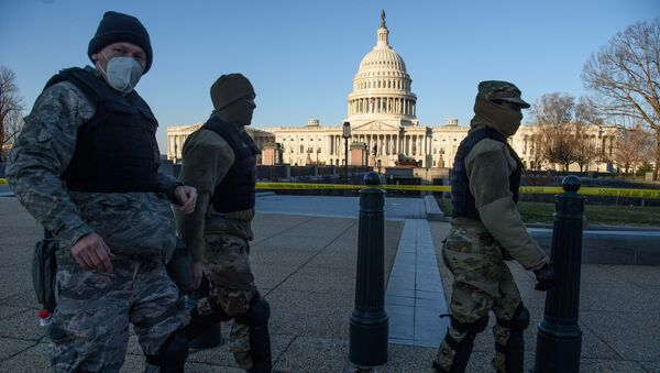 Members of the DC National Guard walk past the US Capitol in Washington, DC, on January 7, 2021, one day after supporters of outgoing President Donald Trump stormed the building. - Sputnik International