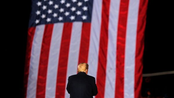 U.S. President Donald Trump stands in front of a U.S. flag while campaigning for Republican Senator Kelly Loeffler on the eve of the run-off election to decide both of Georgia's Senate seats, in Dalton, Georgia, U.S., January 4, 2021. - Sputnik International