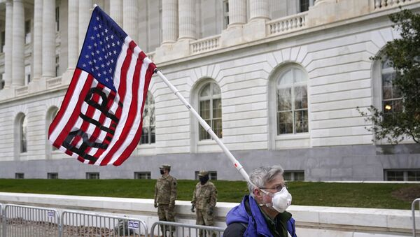 A protester walks past the Russell Senate Office Building on Capitol Hill in Washington, Friday, Jan. 8, 2021. - Sputnik International