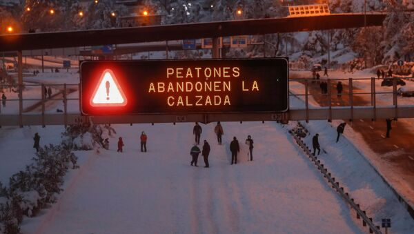 A sign displays a message reading Pedestrians leave the road as people play in the snow on the M-30 motorway, in Madrid, Spain, January 9, 2021. - Sputnik International