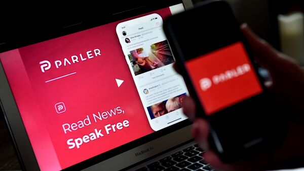 (FILES) In this file photo taken on July 01, 2020 an illustration picture shows social media application logo from Parler displayed on a smartphone with its website in the background in Arlington, Virginia. - Apple on January 9, 2021 - Sputnik International