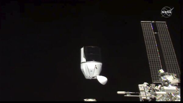 This photo provided by NASA shows SpaceX's Dragon undocking from International Space Station on Tuesday, Jan. 12, 2021.  SpaceX's Dragon cargo capsule undocked with 12 bottles of Bordeaux wine and hundreds of snippets of Merlot and Cabernet Sauvignon vines - Sputnik International