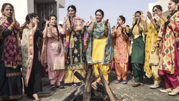 Students in traditional Punjabi dress perform the giddha folk dance around a bonfire on the eve of the Lohri festival in Amritsar on 12 January 2021. - Sputnik International