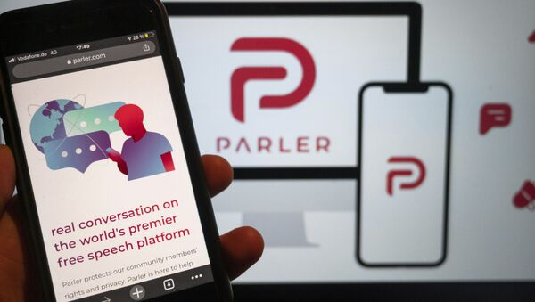The website of the social media platform Parler is displayed in Berlin, Jan. 10, 2021. The platform's logo is on a screen in the background. The conservative-friendly social network Parler was booted off the internet Monday, Jan. 11, over ties to last week's siege on the U.S. Capitol, but not before hackers made off with an archive of its posts, including any that might have helped organize or document the riot.  - Sputnik International