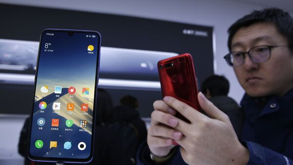 An invited guest takes a photo of Xiaomi's new model MI9 displayed in an exhibition booth after its launch in Beijing on Wednesday, 20 February 2019. - Sputnik International