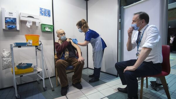 Simon Stevens (R), Chief Executive of the NHS, watches as a nurse (C) administers a dose of the Pfizer-BioNTech Covid-19 vaccine to Frank Naderer (L), 82, at Guy's Hospital in London on 8 December 2020 as the UK starts its biggest ever vaccination programme.  - Sputnik International