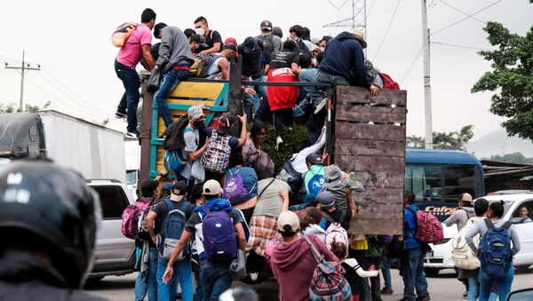 Hondurans climb onto the back of a truck for a ride in a new caravan of migrants, set to head to the United States, in Cofradia, Honduras January 15, 2021. - Sputnik International