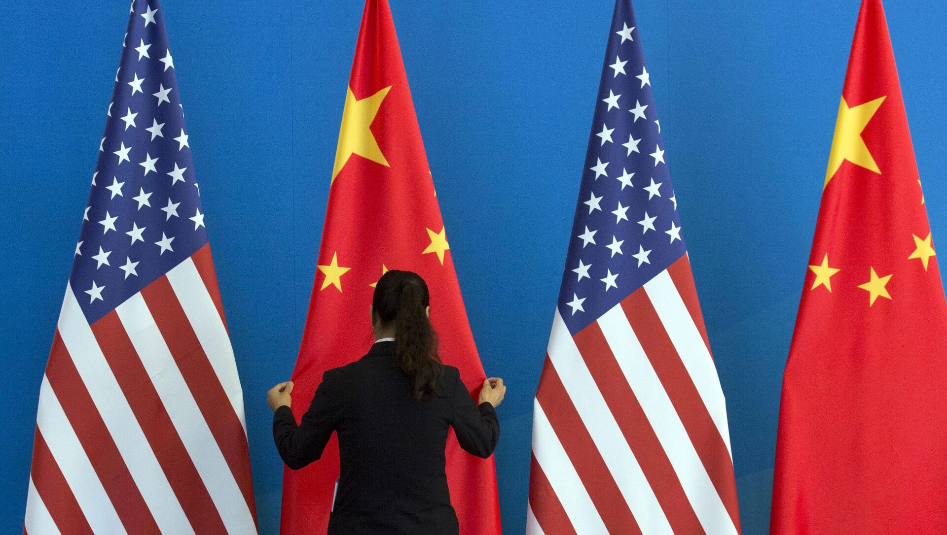 A Chinese woman adjusts the Chinese national flag near U.S. national flags before a Strategic Dialogue expanded meeting that's part of the U.S.-China Strategic and Economic Dialogue at the Diaoyutai State Guesthouse in Beijing, Thursday, July 10, 2014 - Sputnik International, 1920, 11.06.2021
