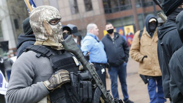 An armed protestor stands outside the Ohio Statehouse Sunday, Jan. 17, 2021, in Columbus, Ohio - Sputnik International
