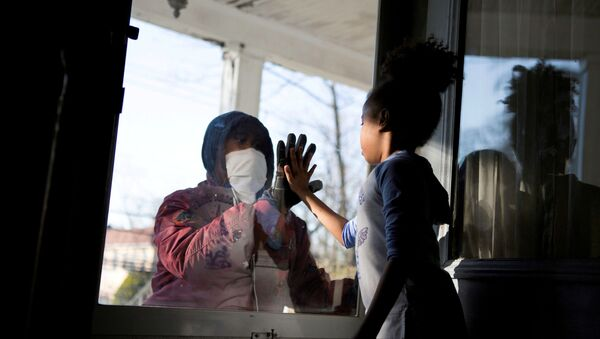 Hashim, an essential worker in the healthcare industry, greets his daughter through the closed door, maintaining social distance from his family as he works with the coronavirus disease (COVID-19) outbreak in New Rochelle, New York, US, 11 April 2020. - Sputnik International
