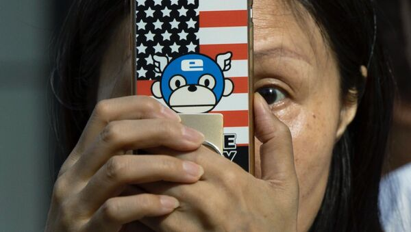 A woman takes a photo with a phone that has a United States flag themed cover outside the United States Consulate in Chengdu in southwest China's Sichuan province on Sunday, July 26, 2020 - Sputnik International