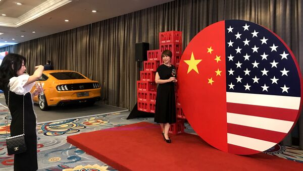 Two women take a photo at a display representing the US and Chinese flags at a reception marking 40 years of diplomatic relations between the US and China, at a hotel in Beijing on June 21, 2019 - Sputnik International