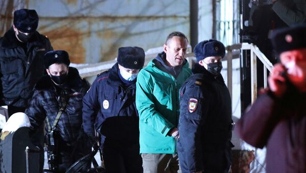 Russian opposition leader Alexei Navalny is escorted by police officers after a court hearing, in Khimki outside Moscow, Russia January 18, 2021. - Sputnik International