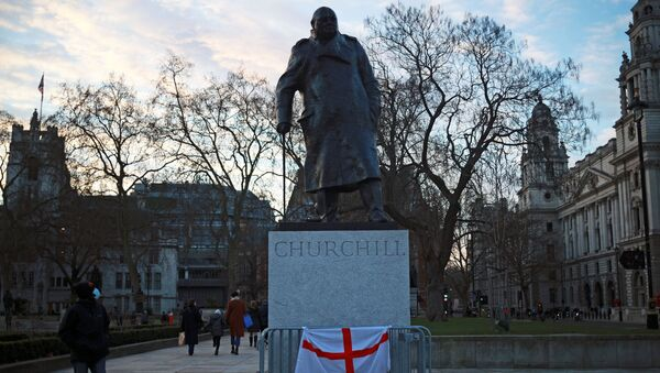 A person wearing a face mask looks at the Winston Churchill statue in Parliament square, in London - Sputnik International