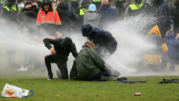 Police uses a water canon during a protest against restrictions put in place to curb the spread of the coronavirus disease (COVID-19), in Amsterdam, Netherlands January 24, 2021. - Sputnik International