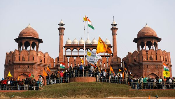 Farmers wave flags during a protest against farm laws introduced by the government, at the historic Red Fort in Delhi, India, January 26, 2021 - Sputnik International