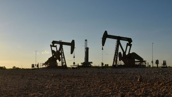 FILE PHOTO: Pump jacks operate in front of a drilling rig in an oil field in Midland - Sputnik International