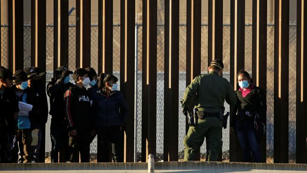 Migrants from Central America are detained by a U.S. Border Patrol agent as they turn themselves in to request asylum, after crossing into El Paso, Texas, U.S., as seen from Ciudad Juarez, Mexico January 22, 2021 - Sputnik International