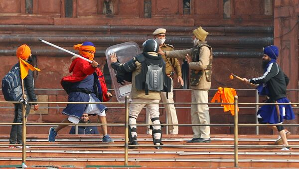 A Nihang (sikh warrior) beats a policeman with a baton during a protest against farm laws introduced by the government, at the historic Red Fort in Delhi, India, January 26, 2021 - Sputnik International