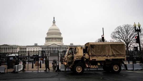U.S. National Guard troops unload food near barbed wire and security fencing around the U.S. Capitol in Washington, U.S., January 26, 2021. REUTERS/Al Drago - Sputnik International