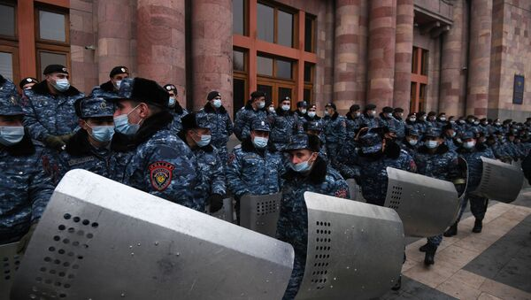Police officers wear protective face masks during a rally demanding the resignation of Prime Minister Nikol Pashinyan, at Republic Square, in Yerevan, Armenia. - Sputnik International