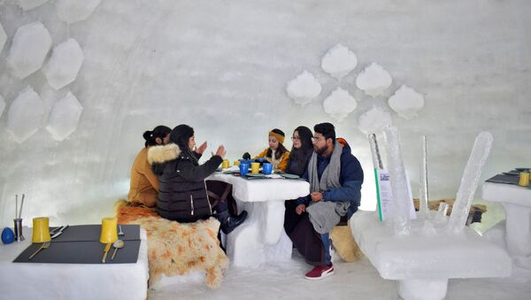 Tourists drink inside Igloo Cafe, a cafe prepared with snow and ice, at Gulmarg, a ski resort and one of the main tourist attractions in Kashmir region, January 28, 2021 - Sputnik International