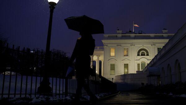 A staff member walks while holding an umbrella under snowfall at the White House in Washington, U.S., February 1, 2021. - Sputnik International