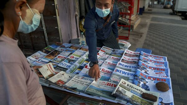 A newspaper seller points at a front-page of a newspaper in Yangon, Myanmar, Tuesday, Feb. 2, 2021. Hundreds of members of Myanmar's Parliament remained confined inside their government housing in the country's capital on Tuesday, a day after the military staged a coup and detained senior politicians including Nobel laureate and de facto leader Aung San Suu Kyi.  - Sputnik International