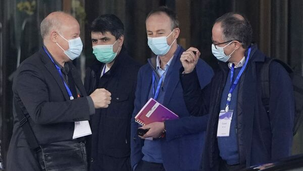 Peter Ben Embarek, right, gestures as Peter Daszak, left, approaches to bump fists with him before they leave the hotel with other members of a World Health Organization team for another day of field visit in Wuhan in central China's Hubei province Tuesday, Feb. 2, 2021 - Sputnik International