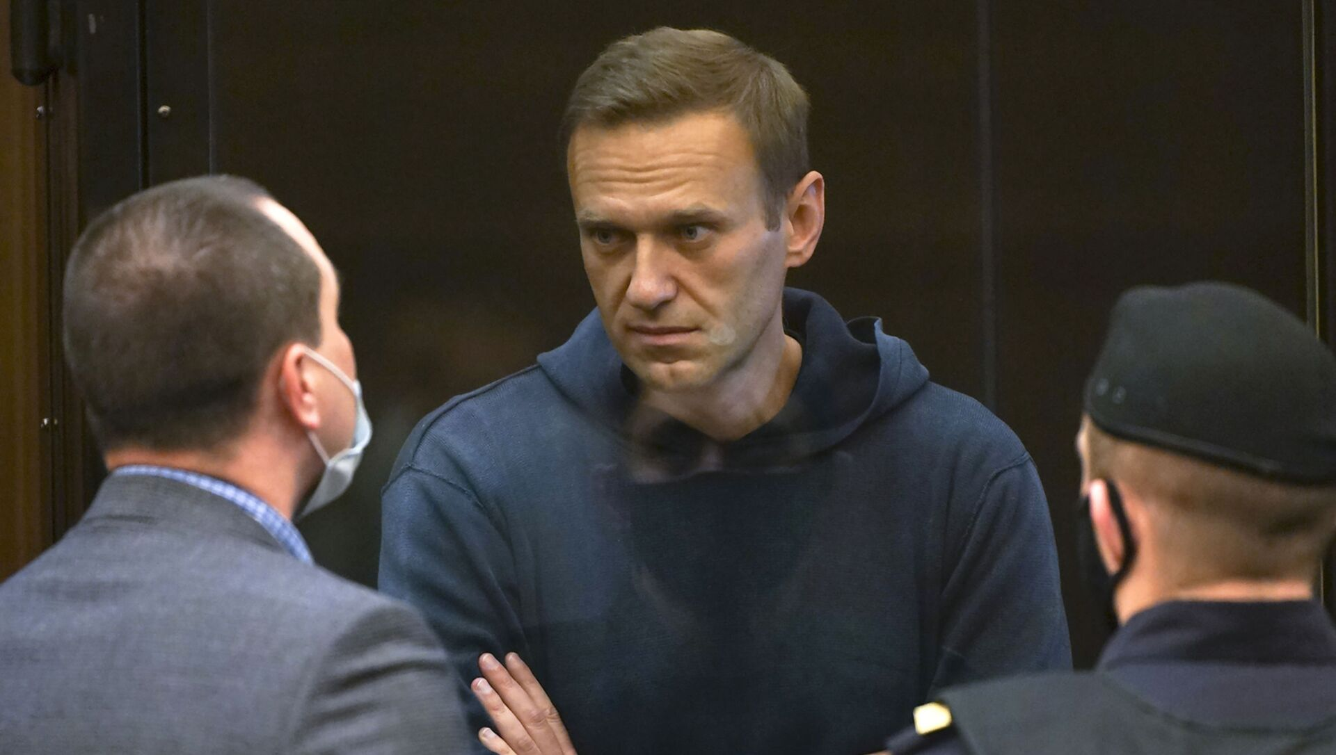 In this handout photo provided by Moscow City Court Russian opposition leader Alexei Navalny talks to one of his lawyers, left, while standing in the cage during a hearing to a motion from the Russian prison service to convert the suspended sentence of Navalny from the 2014 criminal conviction into a real prison term in the Moscow City Court in Moscow, Russia, Tuesday, Feb. 2, 2021. - Sputnik International, 1920, 02.02.2021