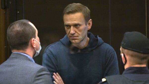 In this handout photo provided by Moscow City Court Russian opposition leader Alexei Navalny talks to one of his lawyers, left, while standing in the cage during a hearing to a motion from the Russian prison service to convert the suspended sentence of Navalny from the 2014 criminal conviction into a real prison term in the Moscow City Court in Moscow, Russia, Tuesday, Feb. 2, 2021. - Sputnik International