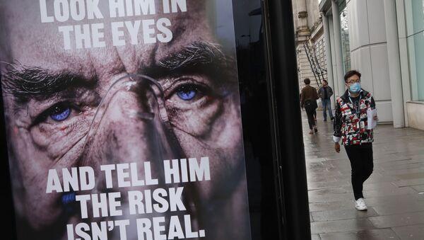 A man wearing a mask against coronavirus walks past an NHS advertisement about COVID-19 in London, Tuesday, Feb. 2, 2021. - Sputnik International
