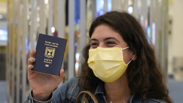 In this Nov. 26, 2020 file photo, an Israeli passenger from a flyDubai flight from Tel Aviv, Israel, waves her Israeli passport on arrival at Dubai International Airport's Terminal 3 in Dubai, United Arab Emirates.  - Sputnik International