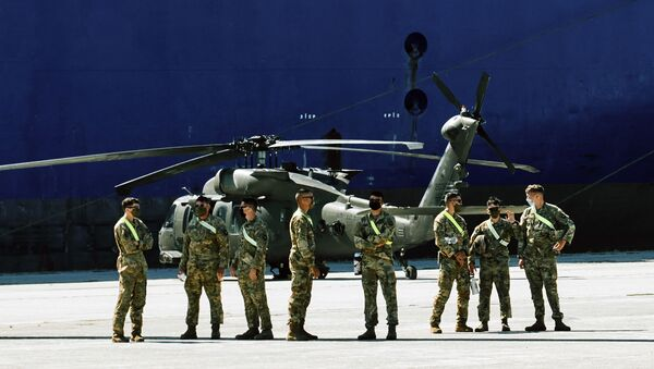 Members of U.S forces stand backdropped by a military helicopter and the U.S. troop carrier Endurance, in the northeast Greek port of Alexandroupolis, near the Turkish border, Thursday, July 23, 2020, where some 2,000 U.S. service members, dozens of helicopters and hundreds of vehicles disembarked - Sputnik International