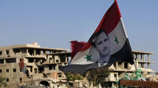 In this July 15, 2018 file photo, a Syrian national flag with a picture of Syrian President Bashar Assad flies at an Army check point, in the town of Douma in the eastern Ghouta region, near Damascus, Syria. - Sputnik International